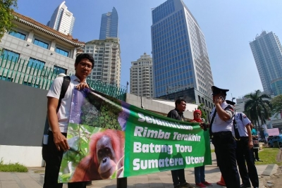 Demonstrators from the Indonesian Forum for the Environment (Walhi) hold a banner protesting China's funding in the Batang Toru dam in front of the Chinese Embassy in Jakarta, Indonesia.
